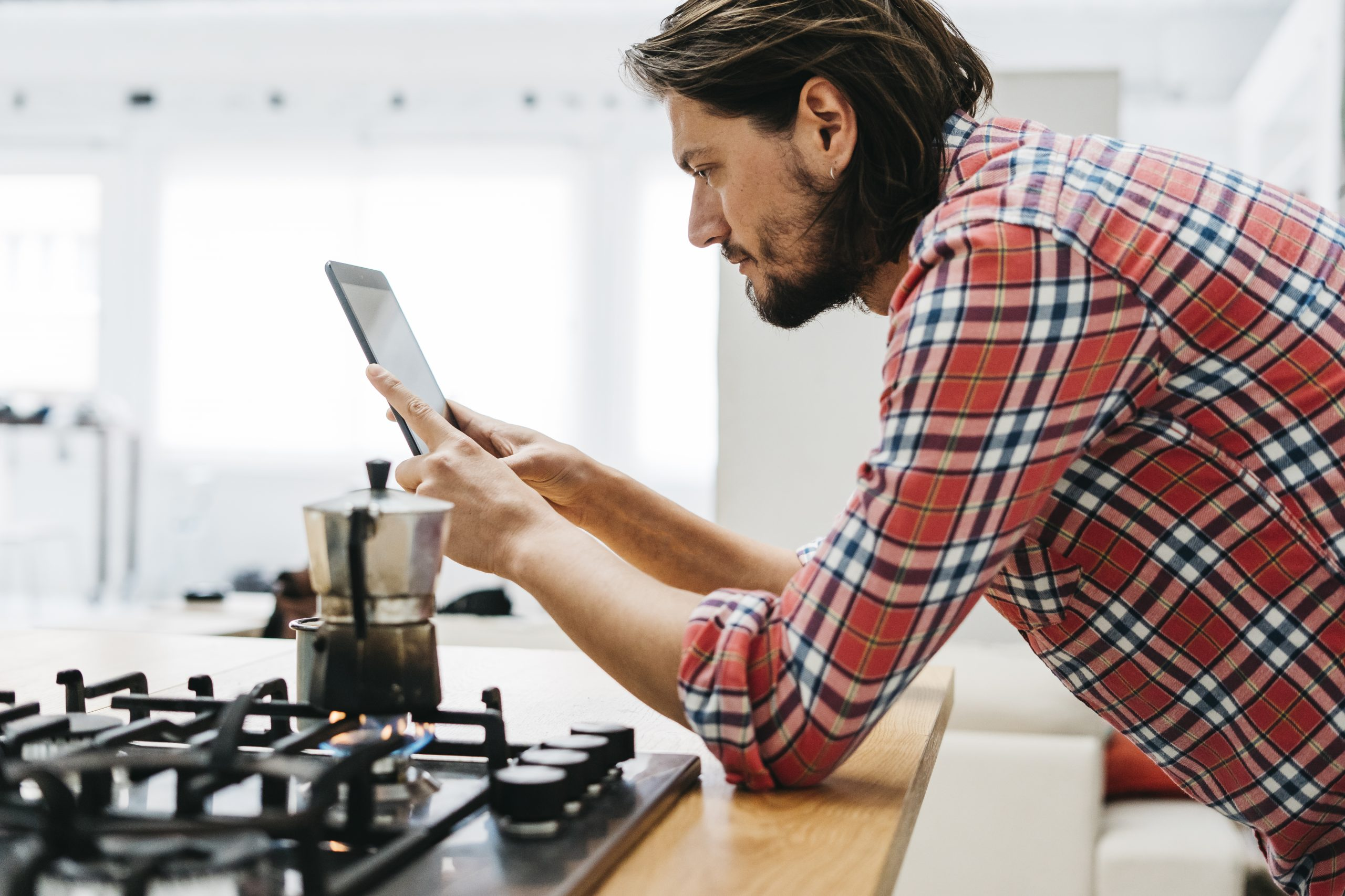 classic-coffee-maker-on-gas-fire-with-man-looking-at-digital-tablet-in-the-kitchen
